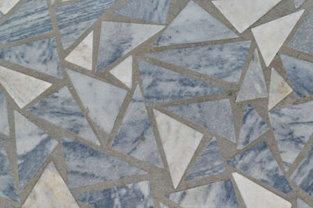 The surface of the floor or wall is made of marble tiles in the form of triangles. The surface is smooth and even. Triangular tiles of different size and color. Texture, background.