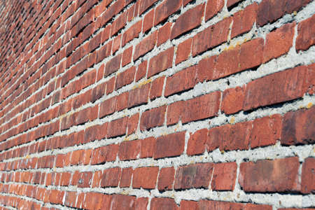 Large red brick wall. Side view. Perspective. The surface of the wall is slightly curved. Brickwork of a large number of bricks. Seams from a thick layer of cement mortar.