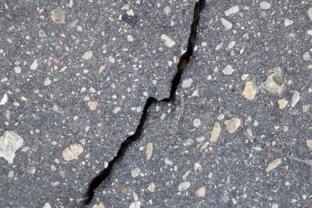 Vertical broken crack on the surface of asphalt pavement. The crack is diagonal and bisects. Gray asphalt with a variety of pebbles of different sizes. A symbol of a broken relationship. Concept. Banco de Imagens