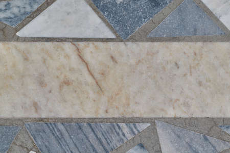 The surface of the floor or wall is made of marble or granite tiles. In the center of the tile rectangular shape. Around the rectangle, the tiles are triangular in shape. The tiles have bands of gray.