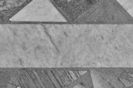 The surface of the floor or wall is made of marble or granite tiles. In the center of the tile rectangular shape. Around the rectangle, the tiles are triangular in shape. Monochrome image. Banco de Imagens
