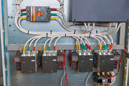 Four magnetic starters, a power circuit breaker and other electrical equipment are connected by electrical wires and cables in an electrical Cabinet. Automation, remote control of electrical networks.