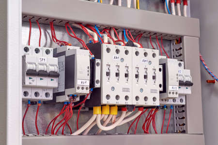 Two power electrical contactors, phase control relays and circuit breakers in the electrical Cabinet. Wires are connected to starters, relays and switches. Manufacture, repair, adjustment, automation. Banco de Imagens