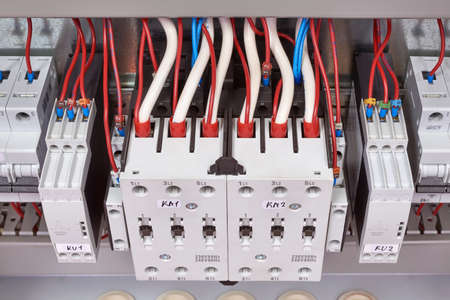 Electrical cables and wires are connected from the top to the contactors or starters and relays of control of phases. Contactors are combined in a reversible Assembly. Modern technology. Banco de Imagens