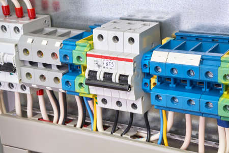 The three-phase circuit breaker is installed in the same row with the connection terminals in the electrical Cabinet. Cables, wires are connected to the switch and terminals. Production, adjustment. Banco de Imagens