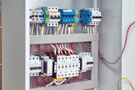 Reversible Assembly of two power contactors, phase control relays, circuit breakers in the electrical Cabinet. Electrical cables and wires are connected to the electrical equipment.