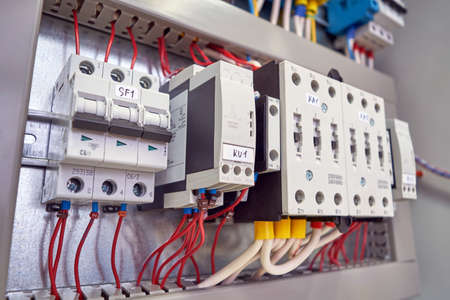 The circuit breaker, phase control relays and power contactors are arranged in a row in the electrical Cabinet. Marked cables and wires are connected to the switch, relays and contactors. Banco de Imagens