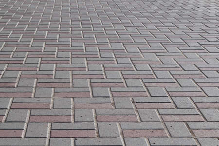 The surface of the pavement paved with paving stones of rectangular shape. The pavers are lined with a pattern. Tiles are gray and brown. Background or backdrop.
