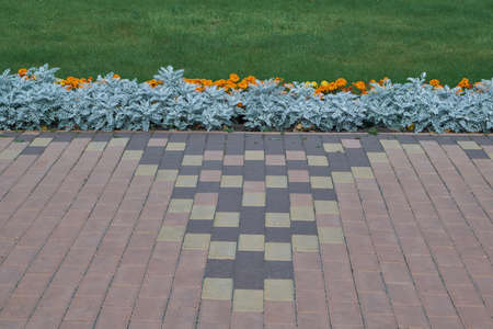 Paving stones laid out in a pattern along the flowerbed with flowers and green grass. Paving stones of rectangular shape. The flowers are orange and yellow. Background or backdrop.