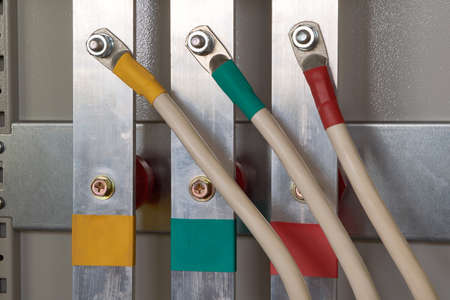 Three electrical cables are connected to a vertical aluminum busbar in the electrical Cabinet. The busbars and the wires marked by color. Busbars are fixed to insulators. Electricity distribution.