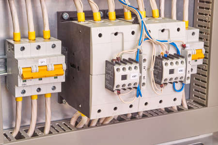 Two powerful power contactors with front additional contacts and two circuit breakers in the electrical Cabinet. Electrical wires are connected to electrical equipment according to the scheme.