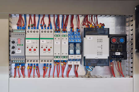 Digital input module, voltage, skew and phase sequence relay, level relay, thermistor protection relay, intermediate relays and thermostat in the electrical Cabinet. Stock Photo