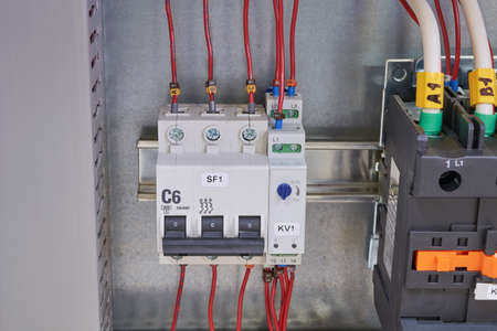Modular circuit breaker, adjustable phase control relay and contactor or magnetic starter in the electrical Cabinet. Marked wires and cables are connected to electrical equipment.