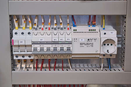 Fuse holder, two circuit breakers, power supply and socket in the electrical Cabinet. The wires and cables are connected to the electrical equipment and laid in the cable channel.