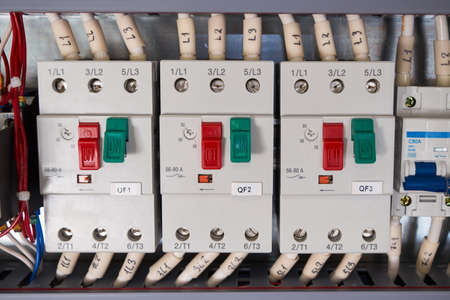 Three automatic motor protection switches with connected wires in the electrical Cabinet. The switches are arranged in a row. There is an adjustment of the current of the electric load.