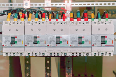 The number of high-power electric circuit breakers molded case circuit breakers in an electrical closet. Electrical cables or wires are connected to the switches. The cables are marked with color.