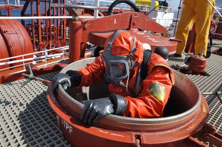trucizna: człowiek w garnitur chemicznych wchodzących wewnątrz zbiorników ładunkowych statku chemicznych do czyszczenia operacji