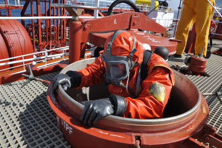 protective suit: man in chemical suit entering inside cargo tank on chemical ship for cleaning operation Stock Photo