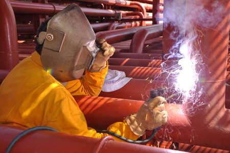 welding metal:  welder works on deck of chemical tanker Stock Photo