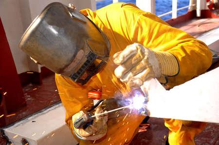 welder works on deck of ship photo
