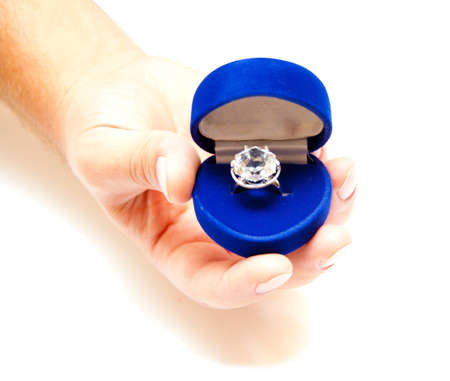 blue jewelry box with ring in the hands on white