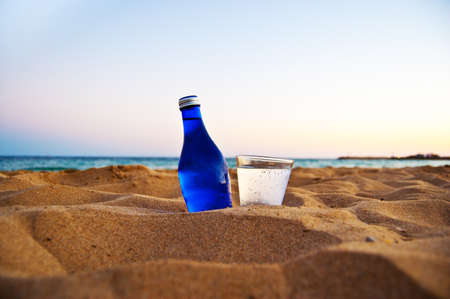 bottle and glass with cold soda on the beach