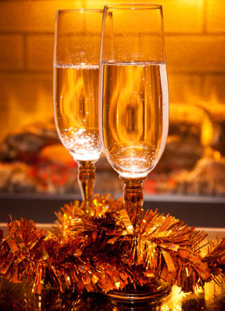 two glasses of champagne in front of fireplace photo