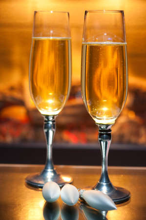two glasses of champagne in front of fireplace