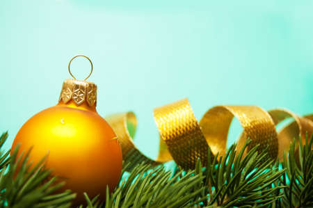 pine branches and christmas ball on turquoise background