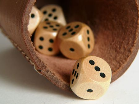 Throwing dices on the white table with the brown leathery dice-box