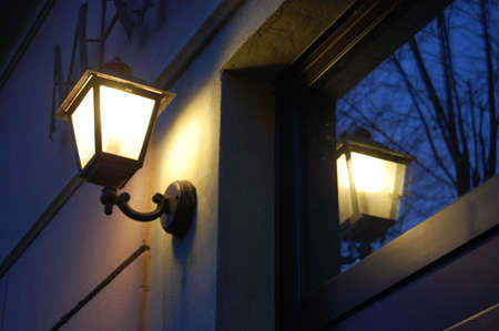 The old street lamp reflecting in the window