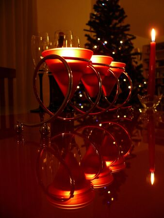 dim light: Lit candles, champagne and glasses reflecting in the glass table in dim light Stock Photo