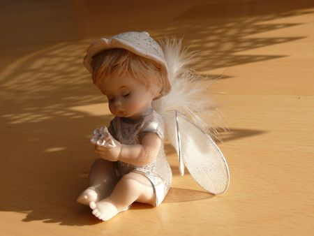 heavenly angel: Little angel figurine illuminated by sun Stock Photo