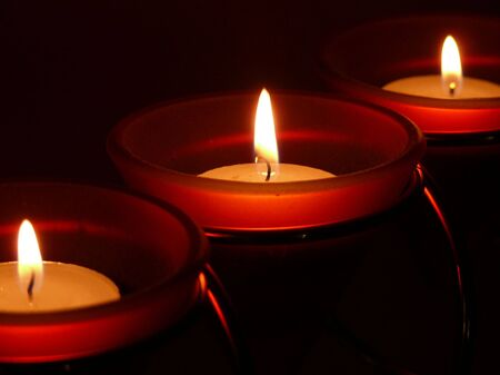 Three candles lit in the dark