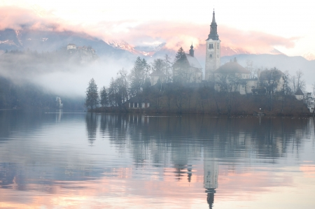 foggy hill: Misty evening at the Bled lake