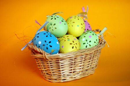 A wicker basket full of colorful easter eggs Stock Photo