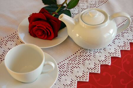 White tea pot, tea cup and a red rose on a saucer photo