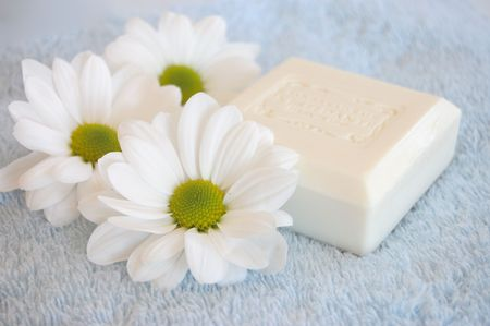 Three white daisies and a soap on a blue towel