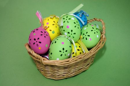 A wicker basket full of colorful easter eggs on a green background photo