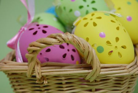 Closeup of a wicker basket full of colorful easter eggs on a green background photo