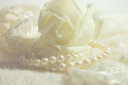 Delicate white rose and a pearl necklace on a lacy bridal lingerie
