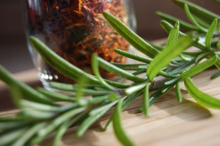 Fresh rosemary on a kitchen table with a bottle of herbs in the background Stock Photo