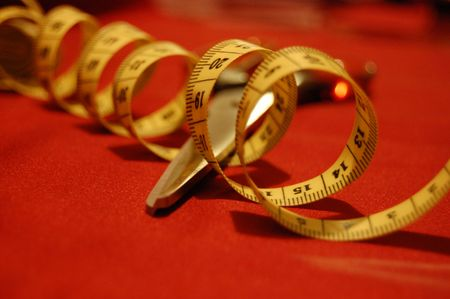 out of production: Closeup of scissors and measuring tape on a red cloth