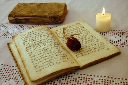 Dried red rose on an open old book by the candlelight with an old book in the background photo