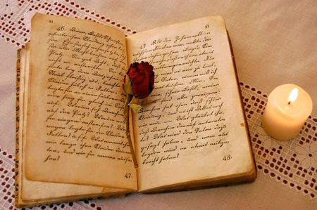 Dried red rose on an open old book by the candlelight Stock Photo