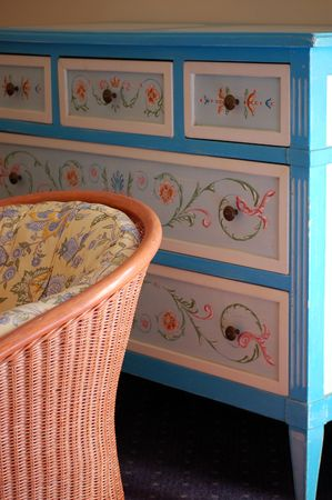 chest of drawers: A beautifully painted chest of drawers and a comfortable chair