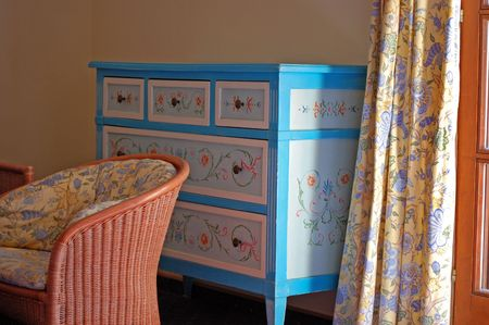 comfortable chair: A beautifully painted chest of drawers and a comfortable chair by the window