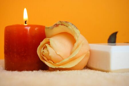 Aromatic candle, apricot rose and natural soap on an apricot towel with an orange background photo