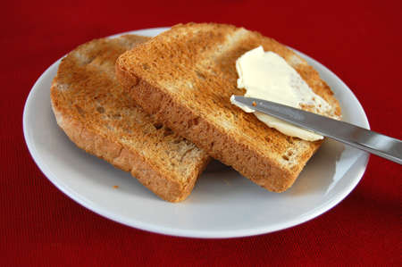 Spreading butter with a knife on a toast photo