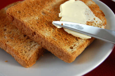 Spreading butter with a knife on a toast Stock Photo